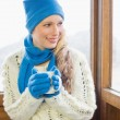 Woman with coffee cup in warm clothing against window — Stock Photo #36274709