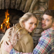 Romantic young couple in front of lit fireplace — Stock Photo