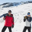 Smiling couple carrying ski boards on shoulders on snow — Stockfoto
