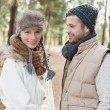 Young couple in winter clothing in the woods — Stock Photo