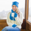 Woman with cup sitting in warm clothing against window — Stock Photo #36275487