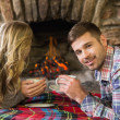Couple with tea cups in front of lit fireplace — Stock Photo #36276583