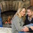 Romantic couple with arms around in front of lit fireplace — Stock Photo