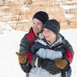 Happy man embracing woman from behind on snow — Stock Photo