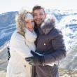 Loving couple in fur hood jackets against snowed mountain range — Stock Photo