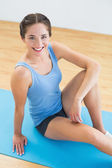 Smiling woman sitting on exercise mat — Stock Photo