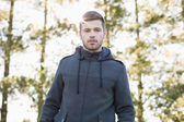 Young man in pullover standing in forest — Stock Photo