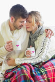 Loving couple in winter clothing with coffee cups — Stock Photo