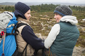 Couple with backpack relaxing while on a hike — Stock Photo