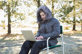 Man in warm clothing using laptop in the forest — Stock Photo