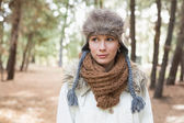 Woman wearing fur hat with woolen scarf and jacket in woods — Stock Photo