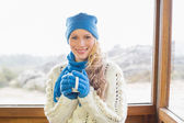 Woman with cup in warm clothing against window — Stock Photo