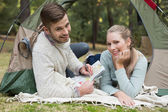 Smiling couple with a map lying in tent — Stock Photo
