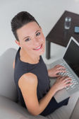Beautiful well dressed young woman using laptop on sofa — Foto Stock