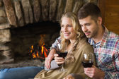 Couple with wineglasses in front of lit fireplace — Stock Photo