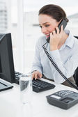 Smiling businesswoman using landline phone and computer in office — Stock Photo