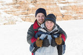 Happy loving couple gesturing thumbs up on snow — Stock Photo