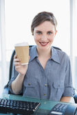 Cheerful young businesswoman presenting disposable cup — Stock Photo