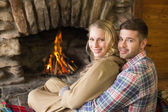 Romantic young couple in front of lit fireplace — Foto de Stock
