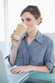 Beautiful businesswoman drinking of disposable cup sitting at her desk — Stock Photo