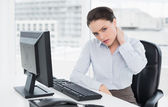 Businesswoman with neck pain sitting at office — Zdjęcie stockowe