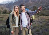Couple with backpacks standing on landscape — Stock Photo