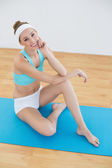 Cute woman posing sitting on blue exercise mat in sports hall — Stock Photo
