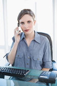 Serious female businesswoman sitting at her desk while phoning — Stock Photo