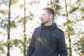 Man in pullover standing in forest against trees — Stock Photo