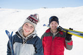 Portrait of a smiling couple with ski boards nn snow — Stock Photo