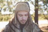 Close-up of a man in warm clothing looking down in forest — Stock Photo