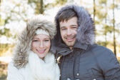 Smiling couple in fur hood jackets in the woods — Stock Photo