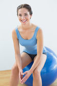 Smiling fit woman sitting on exercise ball — Stock Photo