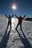 Silhouette couple raising hands with ski poles on snow — Stock Photo