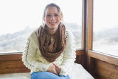 Cute woman sitting in warm clothing in cabin — Stock Photo