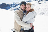 Loving couple in warm clothing on snowed landscape — Stock Photo