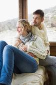 Couple in winter wear looking out through cabin window — Foto de Stock