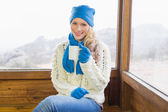 Woman with cup sitting in warm clothing against window — Foto Stock
