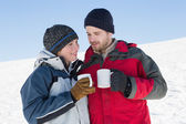 Couple in warm clothing with coffee cups on snow — Stock Photo