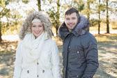 Ler par i päls huva jackor i skogen — Stockfoto