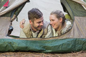Smiling couple lying in tent after a hike — Stockfoto