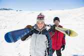 Portrait of a smiling couple with ski boards on snow — Stock Photo