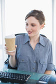 Cute businesswoman looking at disposable cup sitting at her desk — Stock Photo