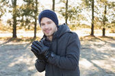 Smiling man in warm clothing shivering while having a walk in fo — Stock Photo