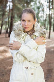 Cute woman shivering while having a walk in a forest — Stock Photo
