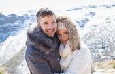 夫妇在夹克拥抱对雪的山 — 图库照片