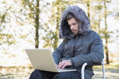 Young man in warm clothing using laptop in the forest — Stock Photo