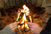 Hands toasting champagne flutes in front of fireplace — Stock Photo
