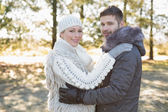 Loving young couple in winter clothing in the woods — Stockfoto