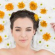 Beautiful young woman with flowers in beauty salon — Stock Photo